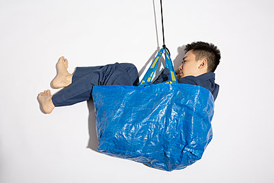 Asian man sitting in blue shopping bag against white background - p817m2179101 by Daniel K Schweitzer