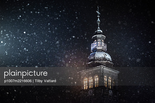France, Le Grand Bornand, Illuminated Church with bell tower at night with snowflakes - p1007m2216606 by Tilby Vattard