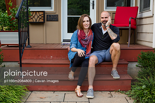 a happy couple sit together on their front stoop - p1166m2084809 by Cavan Images