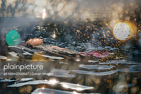 8 years old boy relaxing in a swimming pool - p1166m2292647 by Cavan Images