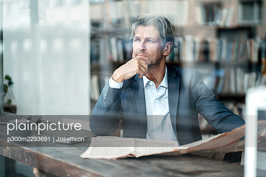 Thoughtful male professional sitting with hand on chin in cafe seen through glass window - p300m2293691 by Joseffson