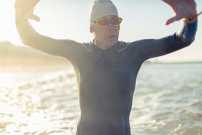 A swimmer in a wet suit, swimming hat and goggles, by the water's edge.  - p1100m1112332f by Mint Images