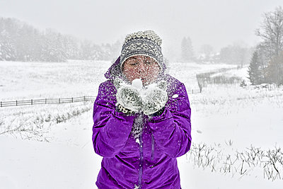 Woman blowing snow while standing on field during snowfall - p1166m1576313 by Cavan Social