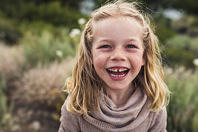 Portrait of happy girl with blond hair standing against plants in forest - p1166m2025001 by Cavan Images