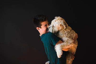 Teenage boy holding a fluffy dog that his licking him on the face. - p1166m2136839 by Cavan Images