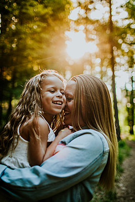 Happy Mom and Daughter laughing and snuggling in backlit forest - p1166m2201883 by Cavan Images