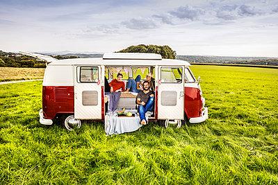 Friends having picnic in a van parked on field in rural landscape - p300m2041839 by Jo Kirchherr