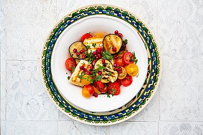 Persischer Tomatensalat mit Halloumi und Auberginen (gegrillt), Granatapfelkernen, Sumach, schwarzem Sesam, Petersilie - p300m2144023 von Larissa Veronesi