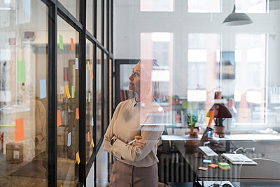 Mature businesswoman looking at adhesive notes on glass pane in office - p300m2154958 by Gustafsson