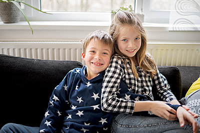 brother and sister cuddle on the couch in the living room and make a selfie and look into the camera during the corona quarantine, lower austria - p300m2180223 von Epiximages