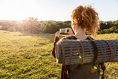 Rear view of woman with backpack photographing field against sky during sunset - p426m1588235 by Kentaroo Tryman