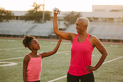 Girl squeezing biceps of grandmother on football field - p555m1304769 by Shestock