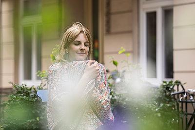 Frau in einer Strickjacke sitzt im Vorgarten - p788m1466146 von Lisa Krechting