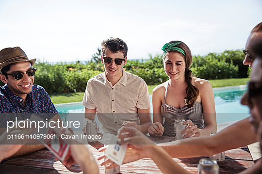 Young people playing cards at table by poolside