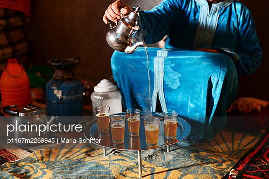 Arab woman pouring tea into tea glasses - p1167m2269945 by Maria Schiffer