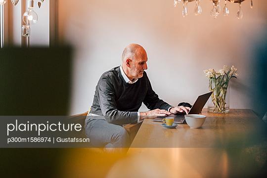 Senior man sitting at home, using laptop - p300m1586974 von Gustafsson