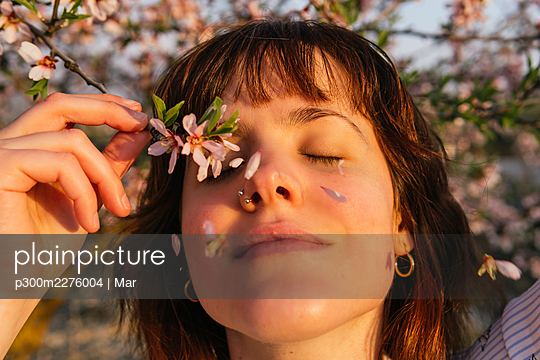 Smiling woman holding almond blossom branch by eyes during sunset - p300m2276004 by Mar