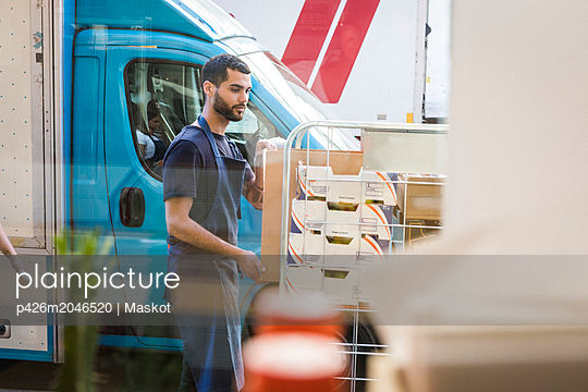 Young male owner standing by rack against food truck seen through restaurant window glass - p426m2046520 by Maskot