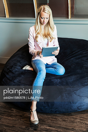 A beautiful young millennial business woman with long blond hair in the workplace using technology; Sherwood Park, Alberta, Canada - p442m1580578 by LJM Photo