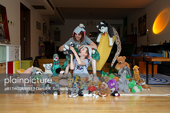 Mother and son with many stuffed animals in the living room - p817m2289851 by Daniel K Schweitzer