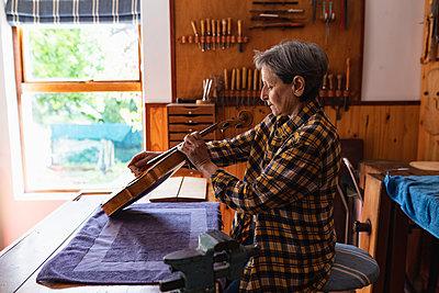 Female luthier at work in a workshop - p1315m2131476 by Wavebreak
