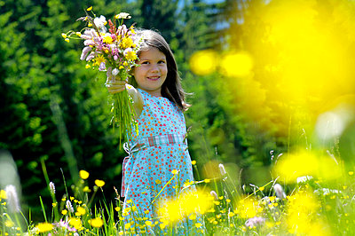 Girl (6-7) holding bunch of flowers in meadow, smiling - p3006389f by Westend61