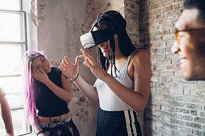 Happy creative team using Vr goggles in loft office - p300m2202840 by Eugenio Marongiu