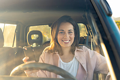 Smiling young woman holding mobile phone in car during sunset - p300m2239905 by VITTA GALLERY