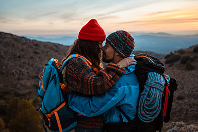 Affectionate couple standing face to face on mountain during sunset - p300m2241665 by Rafa Cortés