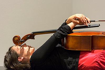 Frau liegt unter einem Cello - p497m754592 von Guntram Walter