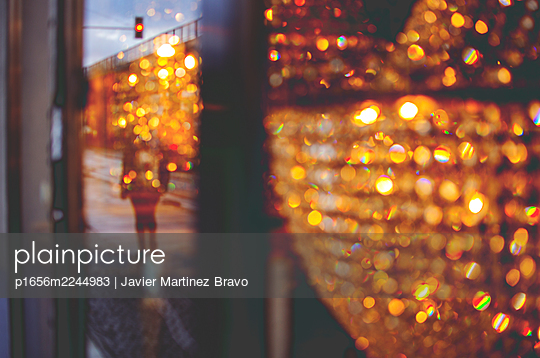brightness of a shop window reflecting a pedestrian walking down the street in a cheerless city on a cloudy and gray day,red traffic light - p1656m2244983 by Javier Martinez Bravo