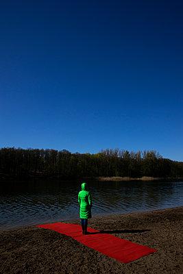 Fraue in grün steht quer auf dem roten Teppich - p1212m1134695 von harry + lidy