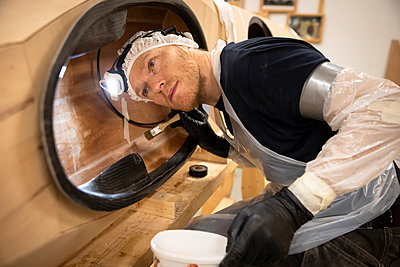 Man with protective clothes using epoxy in kayak - p1687m2278459 by Katja Kircher
