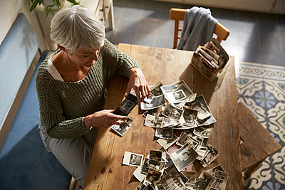 Senior woman sitting at table at home photographing old photos with smartphone - p300m2180050 by Stefanie Aumiller