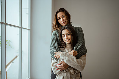 Mother and daughter embracing each other while standing against wall at home - p300m2257174 by Rafa Cortés