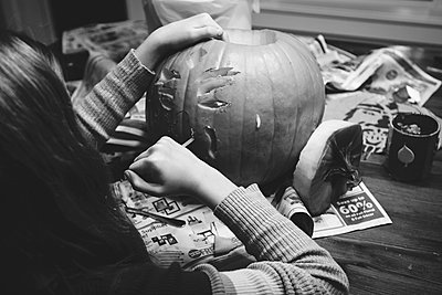 Caucasian girl carving jack-o-lantern pumpkin  - p555m1409662 by Shestock