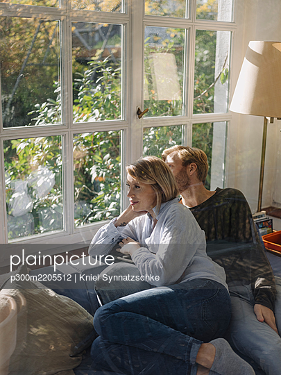 Relaxed couple looking out of window in sunroom at home - p300m2205512 by Kniel Synnatzschke
