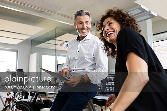 Smiling businessman with digital tablet looking at cheerful colleague while standing at open plan office - p300m2256431 by Peter Scholl