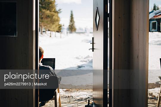 Businessman working seen through doorway - p426m2279913 by Maskot