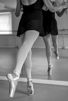 A ballerina joins hands with her own reflection in the mirror of the dance studio. - p1433m2019985 by Wolf Kettler