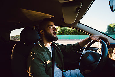 Bearded young man looking at rear-view mirror while driving car - p300m2024190 by Ramon Espelt