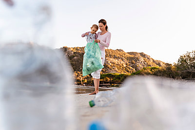 Mother and little daughter collecting empty plastic bottles on the beach - p300m2143715 by Daniel Ingold