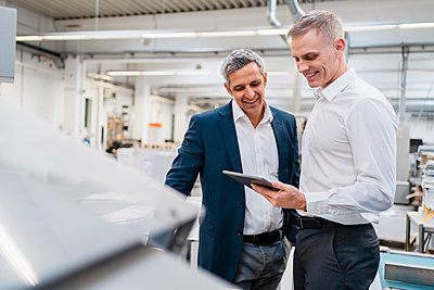 Two smiling businessmen looking at tablet in a factory - p300m2159974 by Daniel Ingold