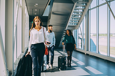 Young businesswoman walking in front of colleagues in corridor at airport - p426m2074496 by Maskot