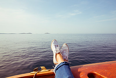 Frau streckt auf Boot Beine aus - p432m2026109 von mia takahara