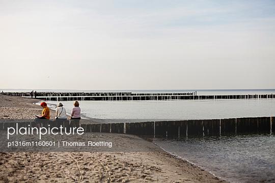 Frauen sitzen auf Buhnen am Strand von Nienhagen, Nienhagen, Mecklenburg-Vorpommern, Deutschland - p1316m1160601 von Thomas Roetting