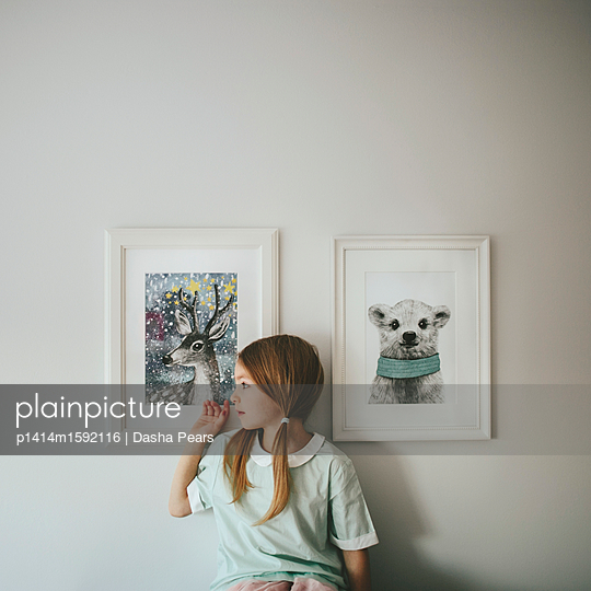 Girl sitting in front of framed pictures - p1414m1592116 by Dasha Pears