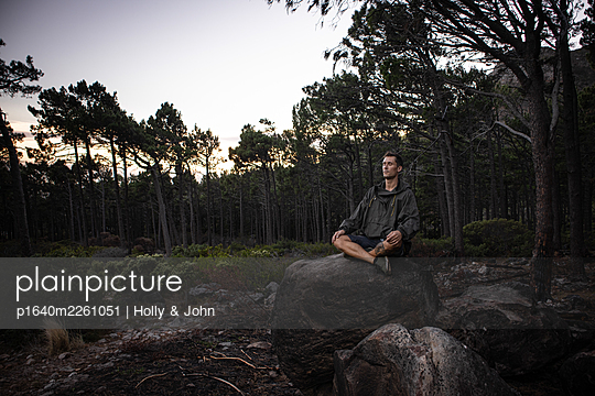 Hiker sits on boulder at twilight - p1640m2261051 by Holly & John