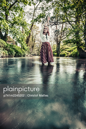 Woman in stylish outfit stands in a river - p741m2245202 by Christof Mattes