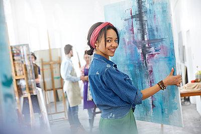 Portrait smiling female artist lifting painting in art class studio - p1023m1506491 by Agnieszka Olek